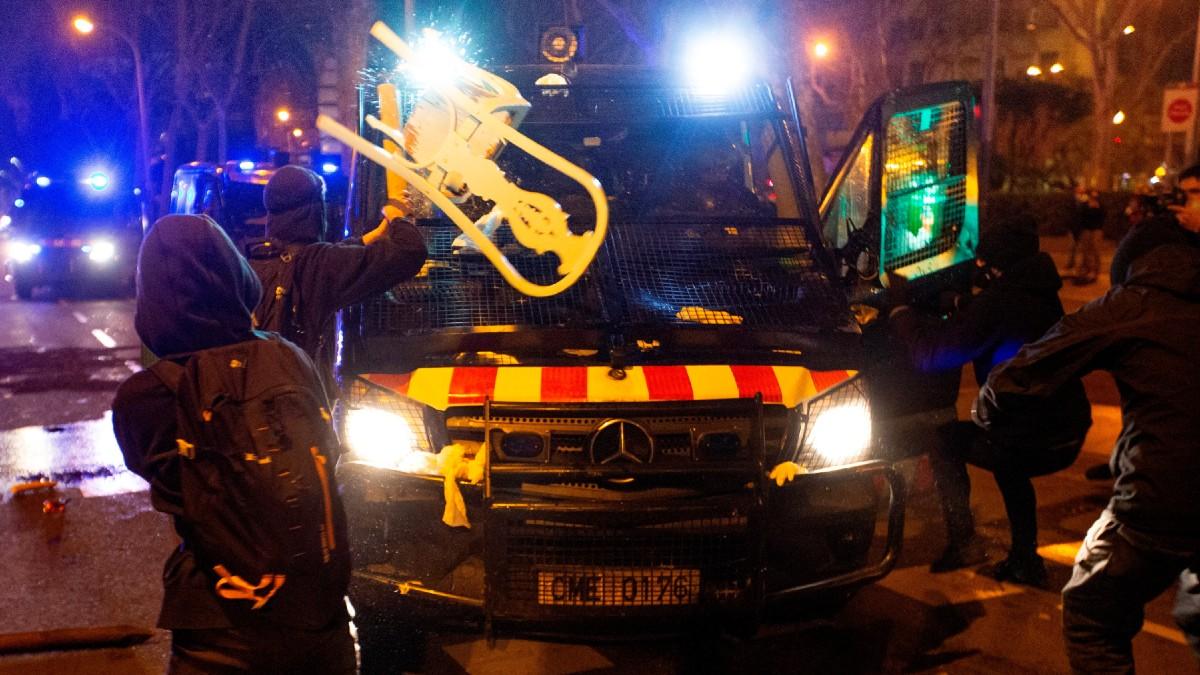 Varios manifestantes lanzan objetos a un vehículo de los cuerpos antidisturbios tras la manifestación de protesta por la detención del rapero Pablo Hasel, condenado por delitos de enaltecimiento del terrorismo e injurias a la Corona. (Foto: Efe)