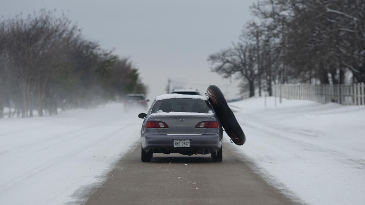 Un vehículo circula por una carretera de Texas cubierta por la nieve.