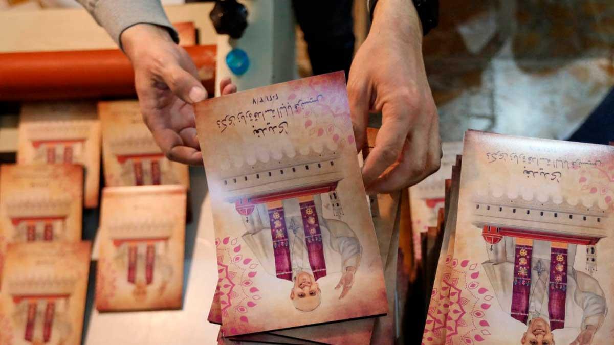 Un comerciante muestra los folletos preparados para la visita del Papa Francisco a Irak. Foto: AFP
