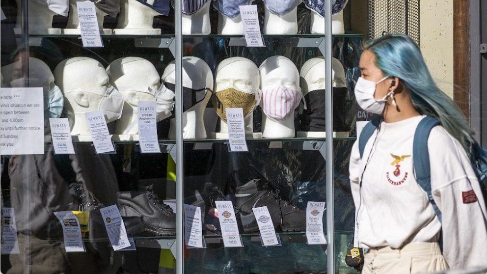 Una mujer con mascarilla pasa ante una tienda (Foto: Jane Barlow/PA Wire/dpa).
