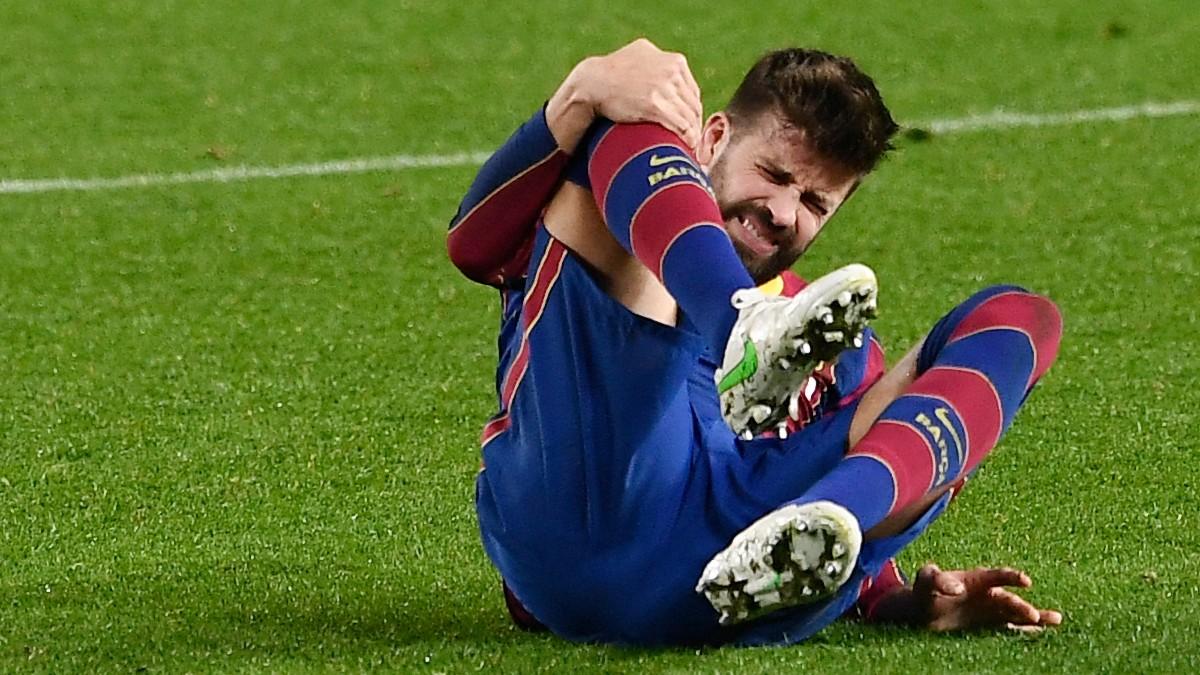 Gerard Piqué se toca la rodilla derecha tras lesionarse ante el Sevilla. (AFP)