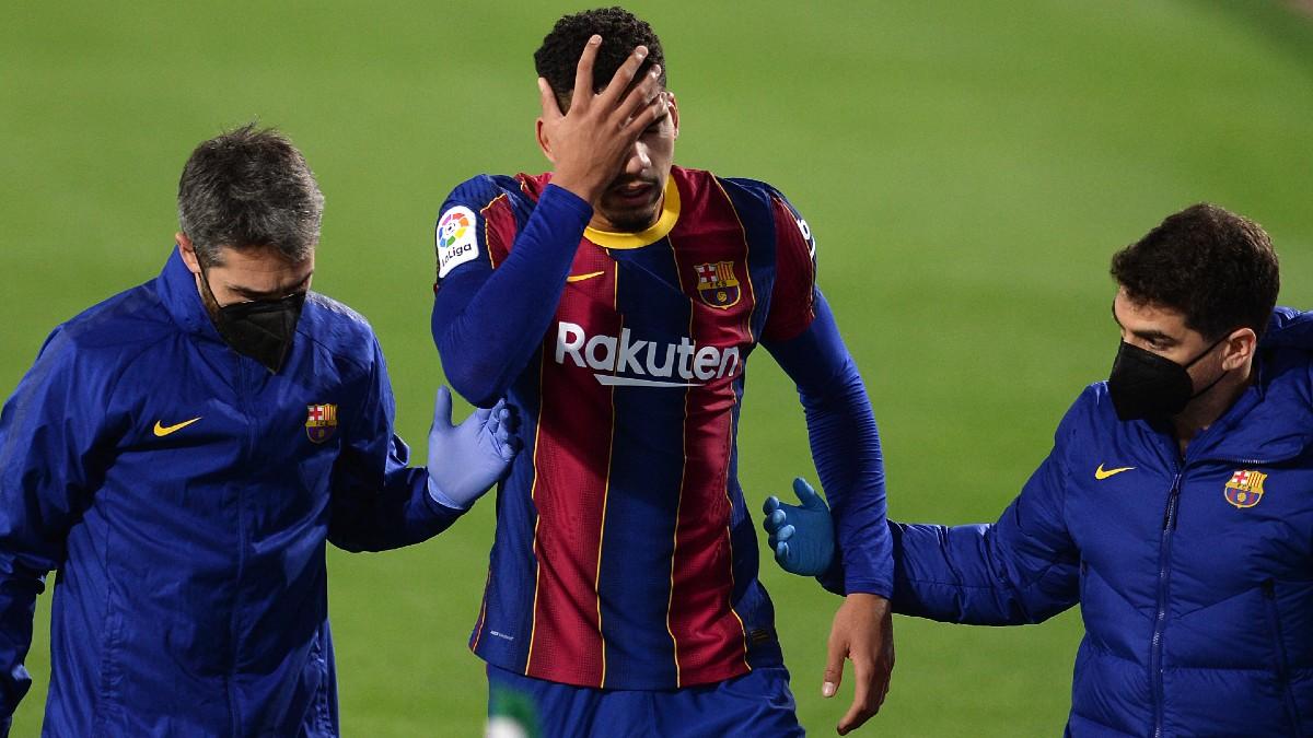 Ronald Araújo se lleva las manos a la cabeza tras lesionarse. (AFP)