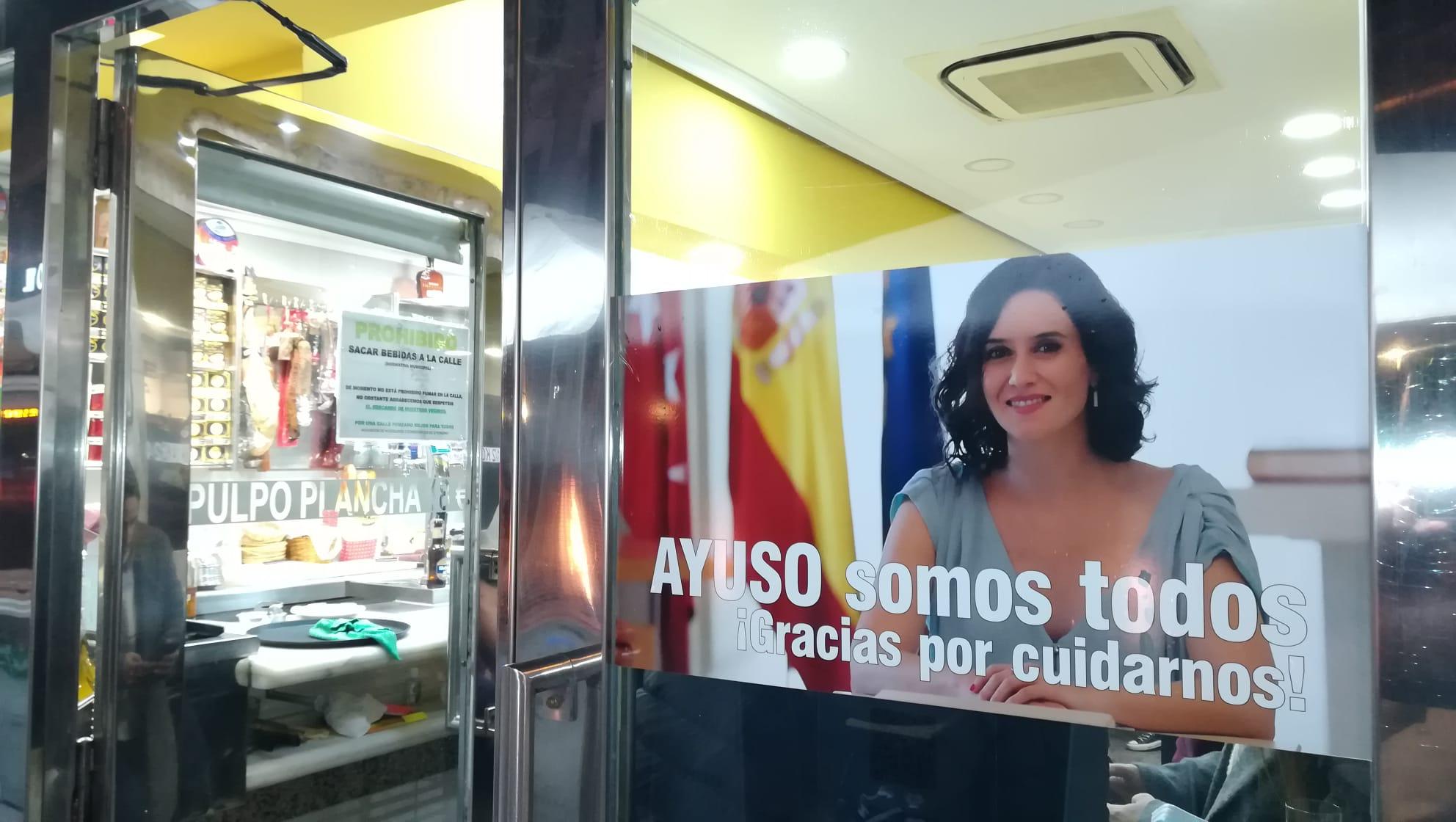 Cartel de apoyo a Isabel Díaz Ayuso en un bar de Madrid.