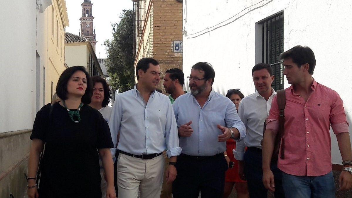 Juanma Moreno, flanquedo por Juan Ávila y Virginia Pérez, en una visita a Carmona (Sevilla).