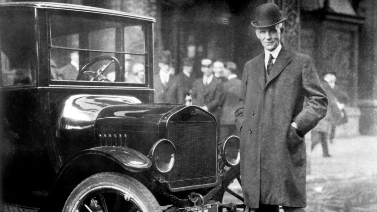 Henry Ford posando junto a un coche