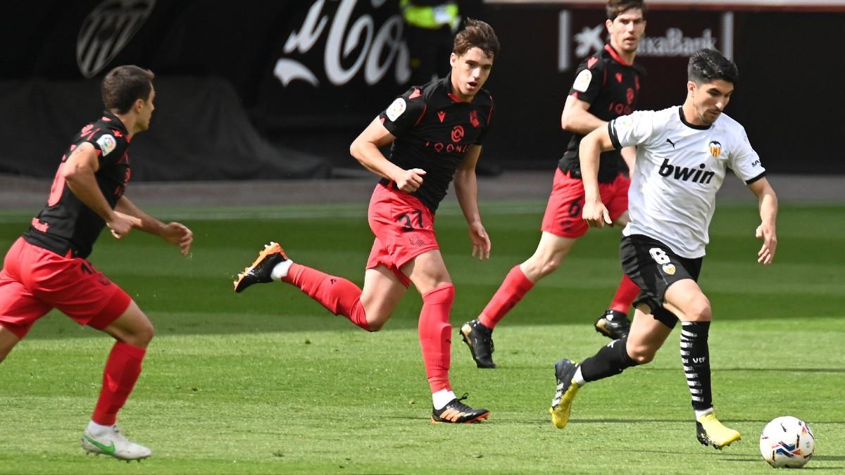 Los jugadores del Valencia y Real Sociedad pelean por un balón. (AFP)