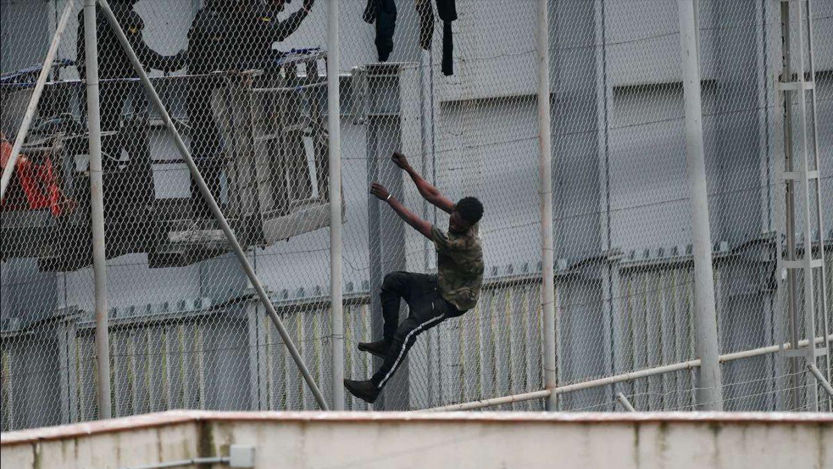 Dos agentes se acercan a un migrante que intenta saltar la valla que separa Ceuta de Marruecos (Antonio Sempere / Europa Press)