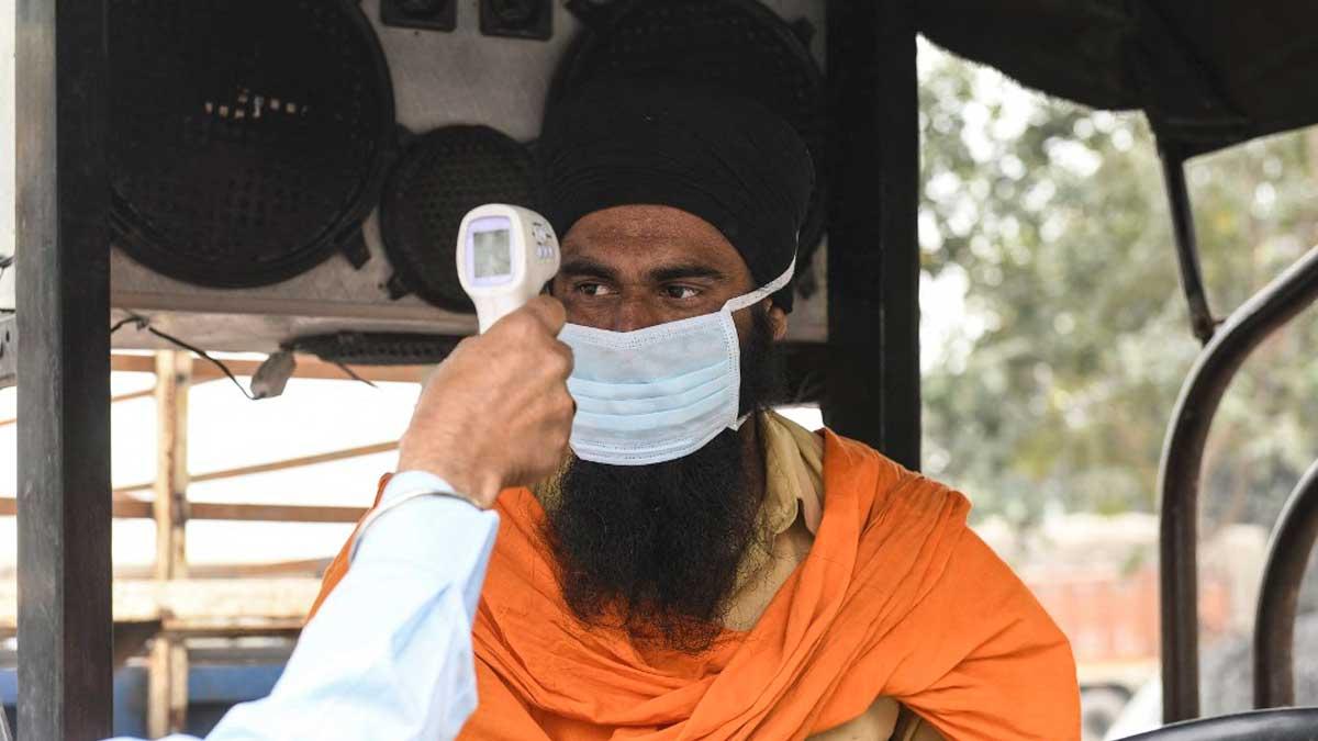 Un sanitario toma la temperatura a un conductor en Amritsar, India. Foto: AFP