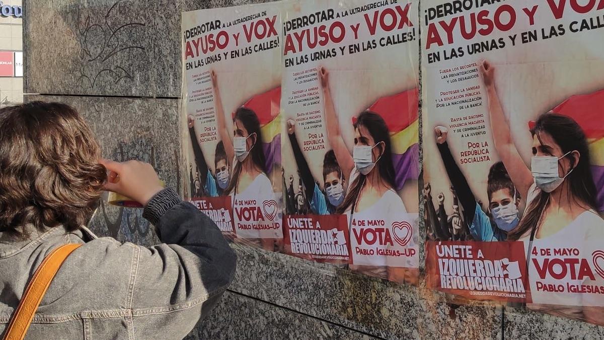Una simpatizante del Sindicato de Estudiantes colocando un cartel a favor de Pablo Iglesias y Unidas Podemos.