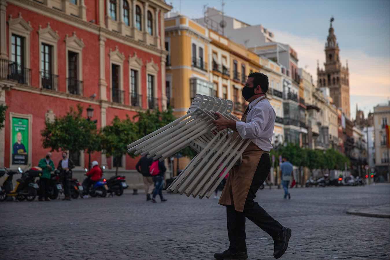 Un hostelero recoge el mobiliario de la terraza de un bar de Sevilla (María José López / Europa Press).