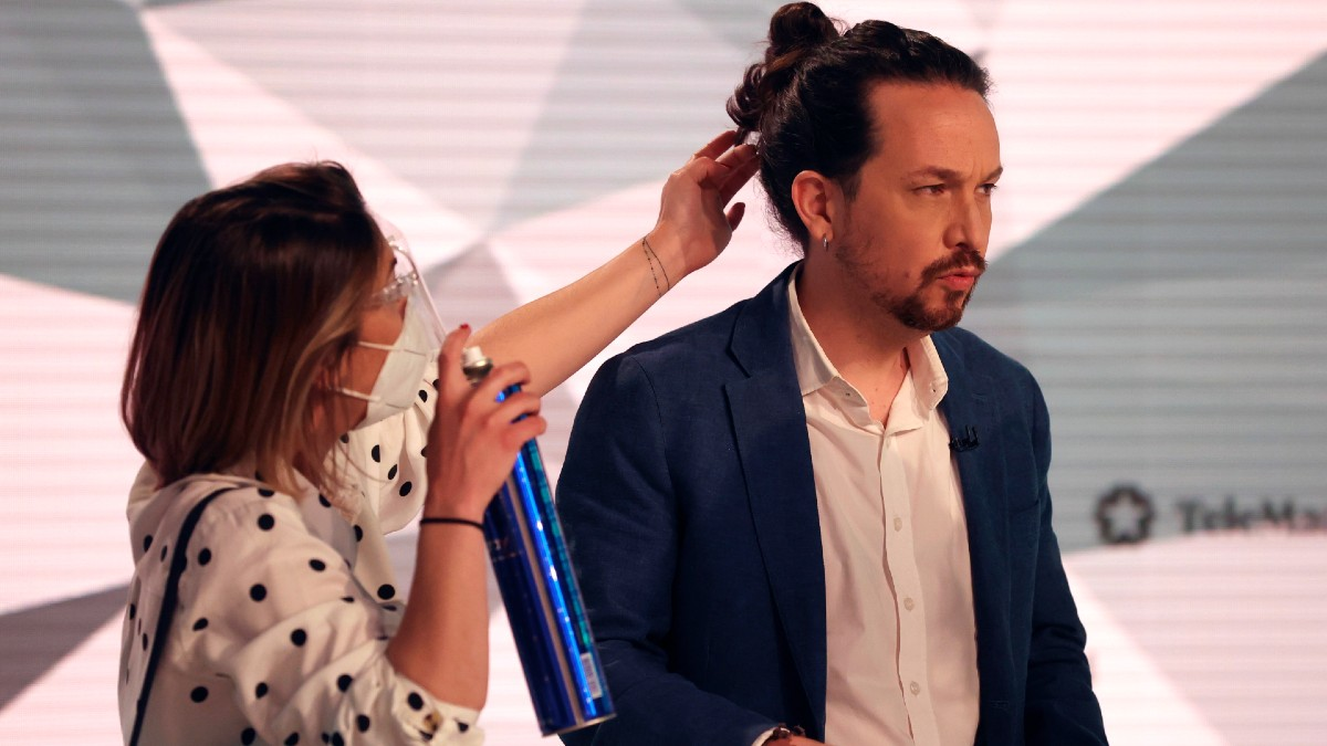Una peluquera retoca el moño de Pablo Iglesias, candidato de Podemos a la Comunidad de Madrid, antes del inicio del debate de Telemadrid. (Foto: Efe)