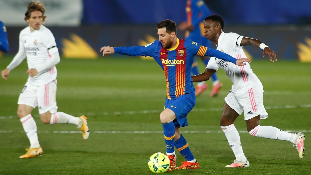 Messi conduce un balón ante la mirada de Modric y Vinicius en el Clásico. (Getty)