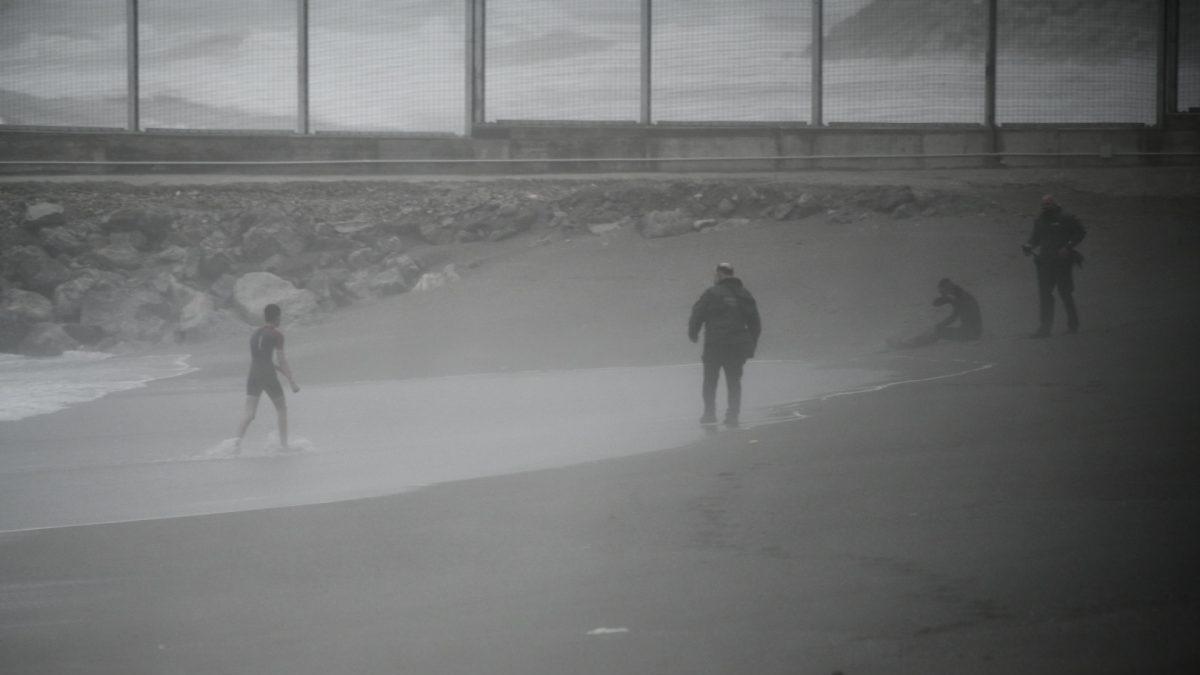 Dos jóvenes migrantes marroquíes llegan a la playa del Tarajal de Ceuta
