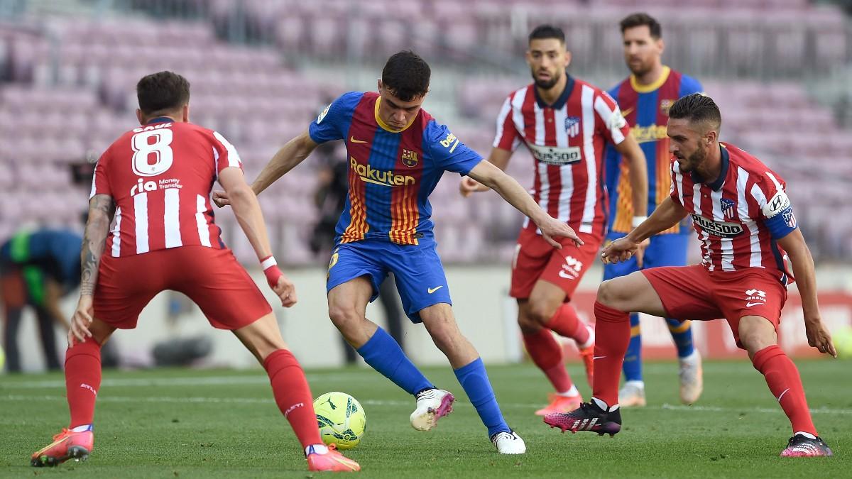 Pedri controla un balón ante la presión de Koke y Saúl. (AFP)
