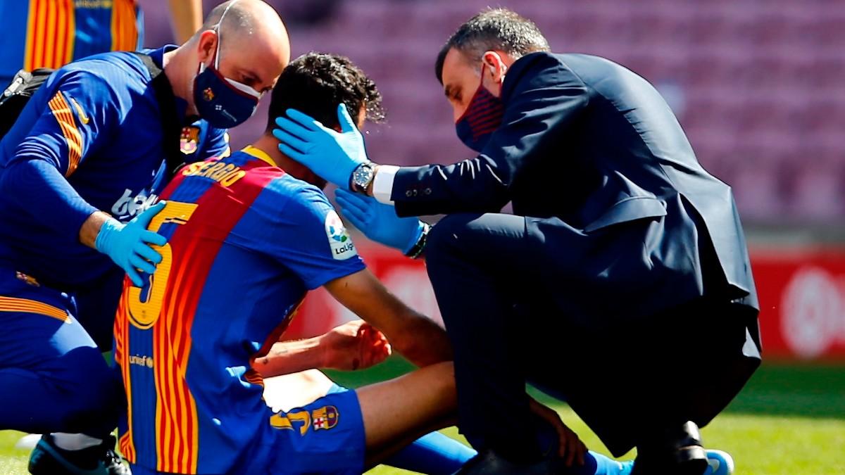 Sergio Busquets es atendido por los doctores tras el choque con Savic. (EFE)