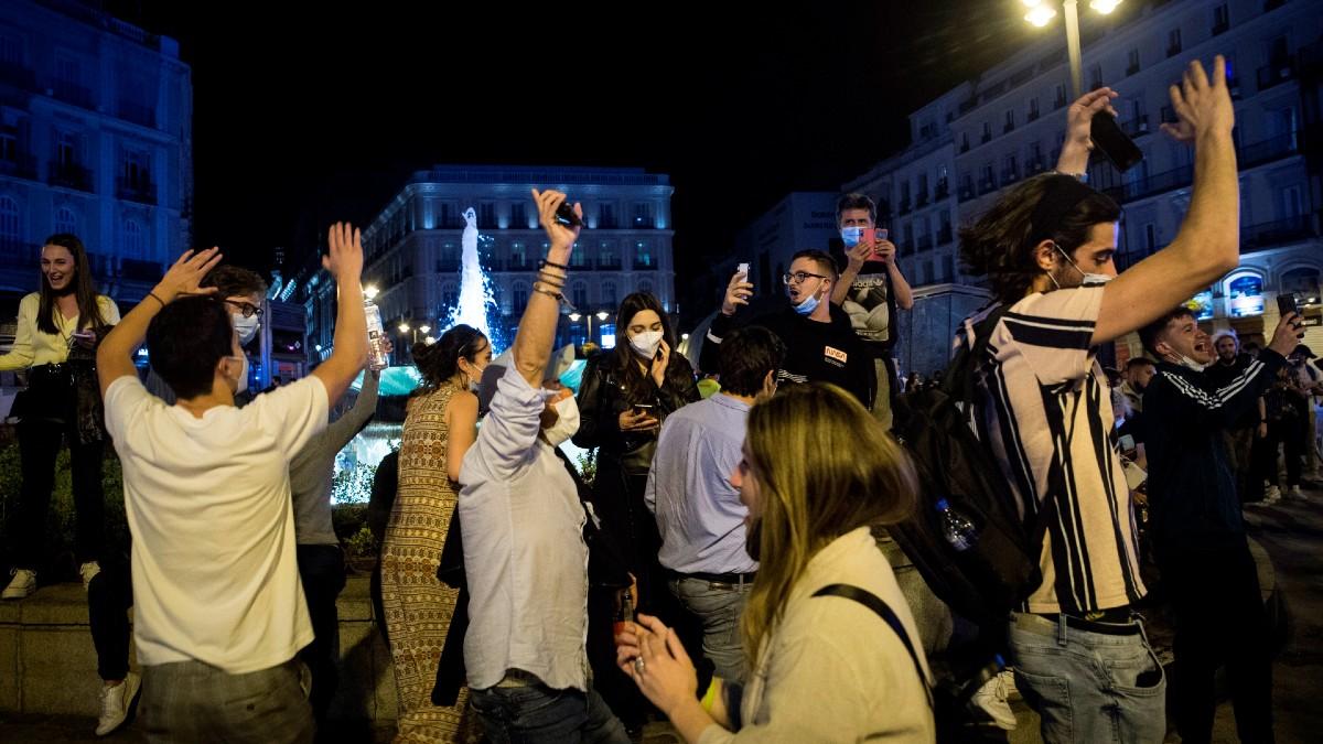 Un grupo de personas celebra el final del estado de alarma en la Puerta del Sol de Madrid.