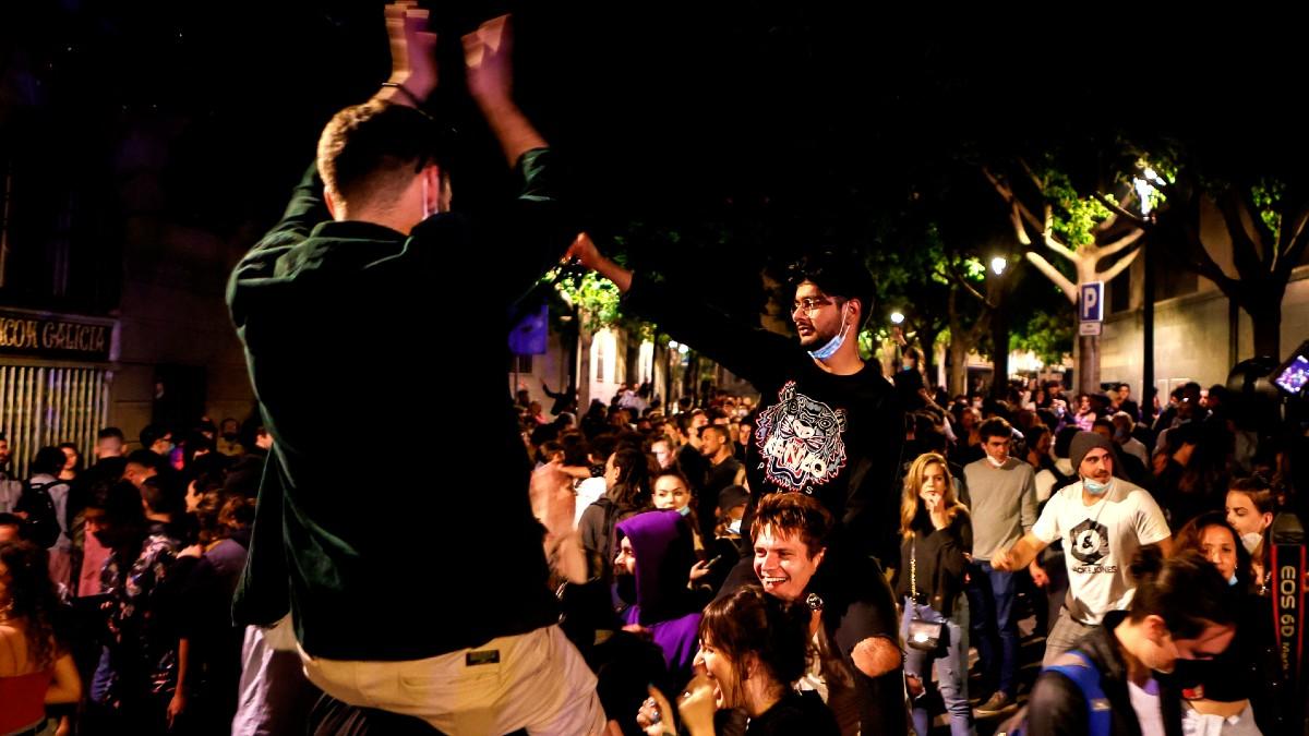 Decenas de jóvenes celebran junto al Passeig de Lluis Companys de Barcelona, el fin del estado de alarma en Cataluña durante la madrugada del domingo. (Foto: Efe)
