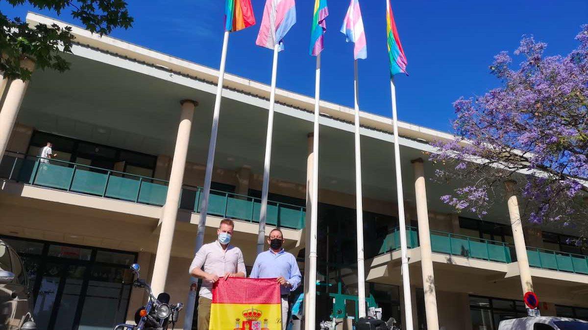 Adrián Trashorras, portavoz de Vox Dos Hermanas, porta la bandera de España junto a un coordinador de su equipo.