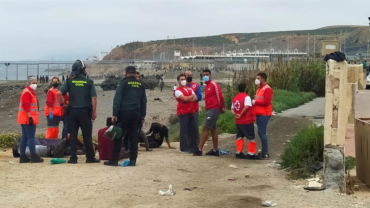 Varios inmigrantes son atendidos por la Cruz Roja en El Tarajal.