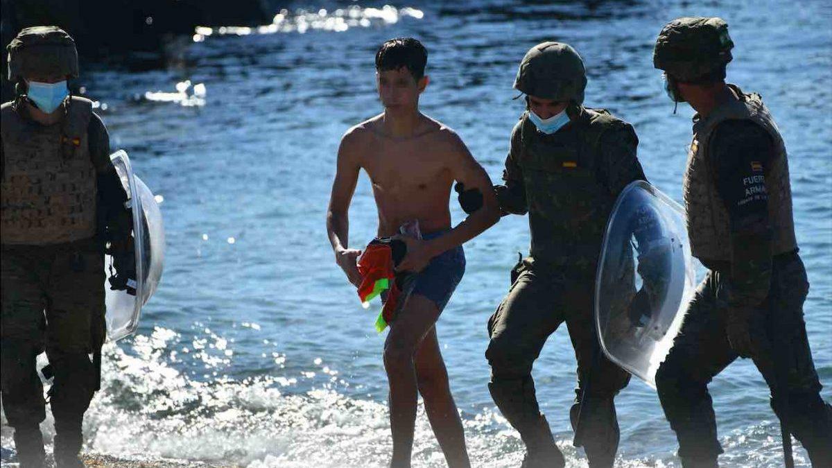 Militares del ejército español ayudan a un mena llegado a Ceuta desde Marruecos (Antonio Sempere / Europa Press).