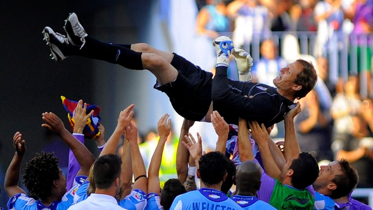 Francesc Arnau, manteado por sus compañeros del Málaga. (AFP)