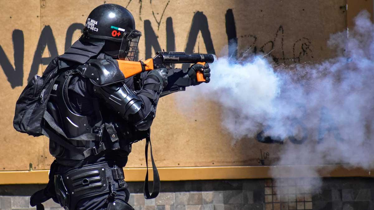 Un Policía dispara gas lacrimógeno a manifestantes en Colombia. Foto: EP