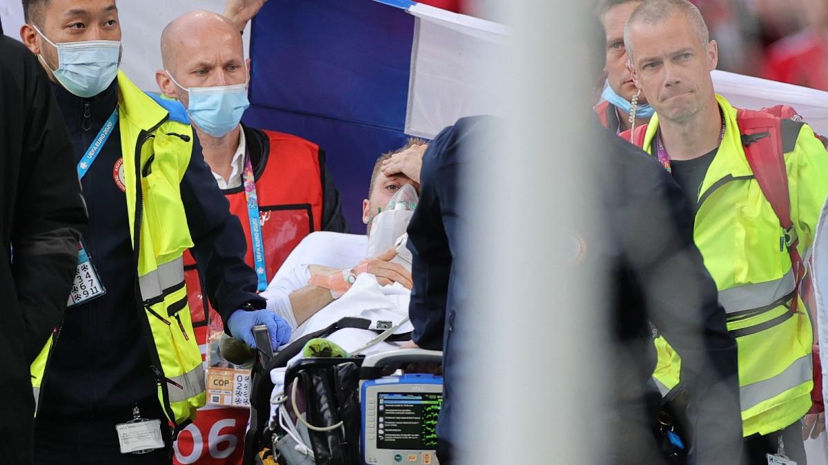 Eriksen, en el momento en el que es retirado del césped. (AFP)