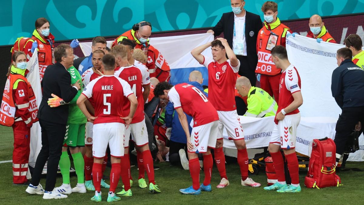El jugador de Dinamarca Christian Eriksen es atendido en el césped. (AFP)