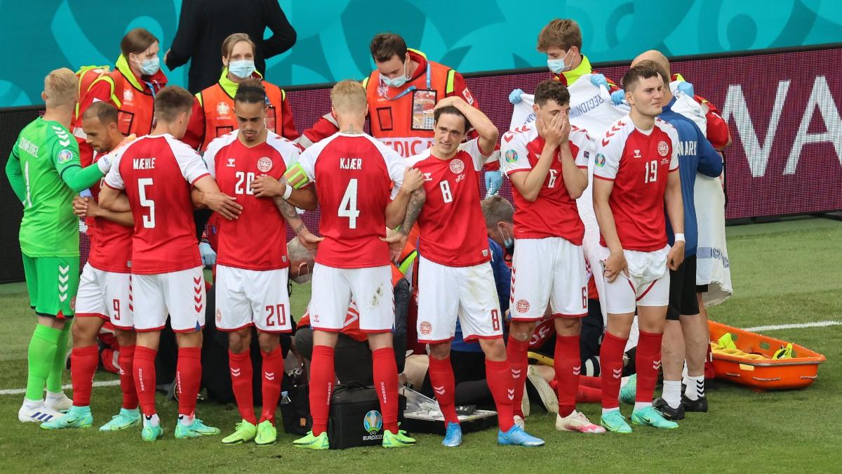 Los jugadores de Dinamarca, alrededor de Eriksen mientras es atendido. (AFP)