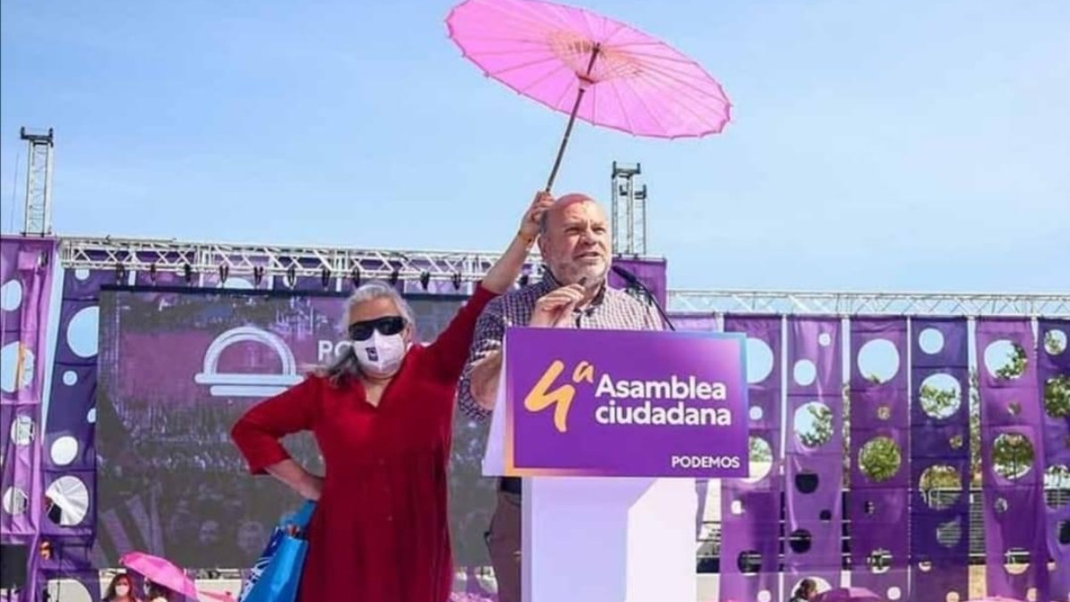La mujer cubre con un paraguas a -un hombre- miembro de Unidas Podemos.