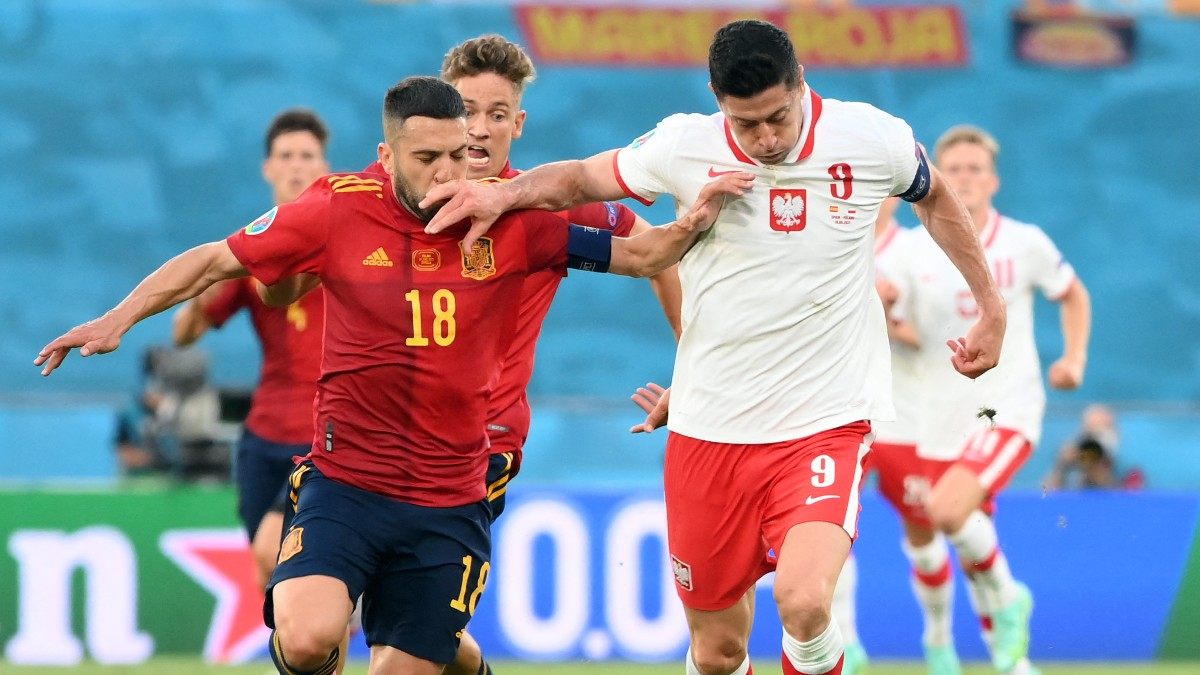 Jordi Alba pelea un balón con Lewandowski. (AFP)