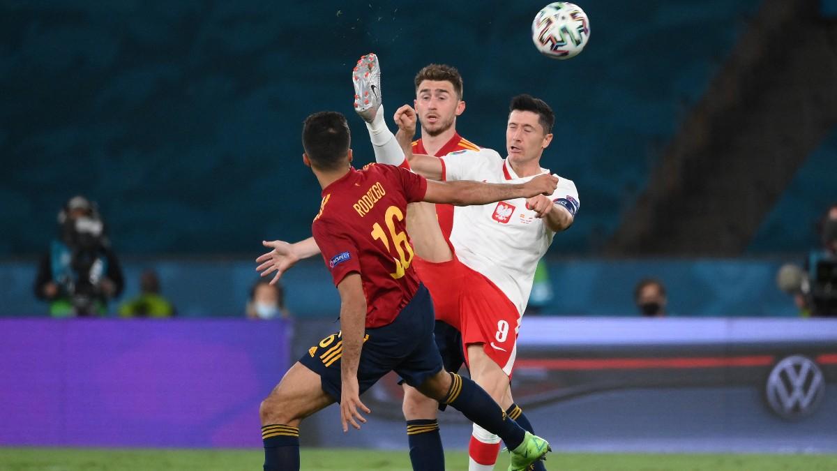 Laporte y Rodrigo pelean con Lewandowski por un balón. (AFP)
