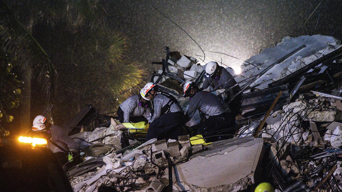 Equipos de rescate retiran un cuerpo entre los escombros del edificio derrumbado en Miami. (AFP)