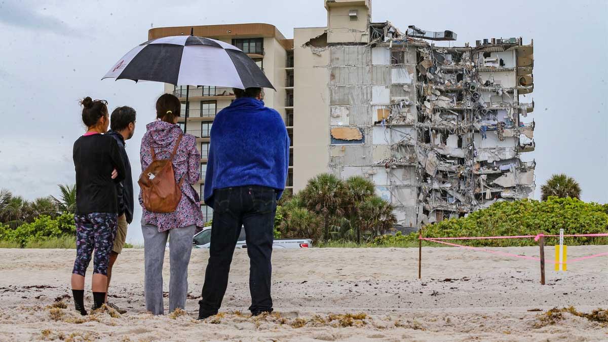 Unos curiosos observan el edificio derrumbado. Foto: Europa Press.