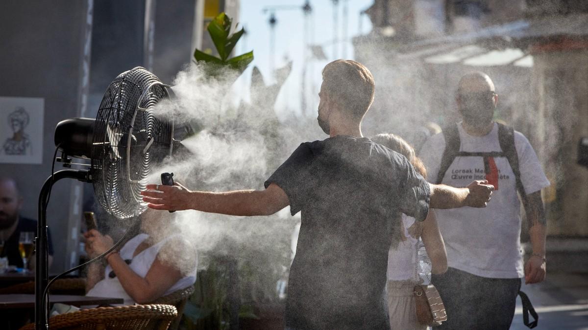 Un chico se refresca del calor con un difusor de vapor de agua.