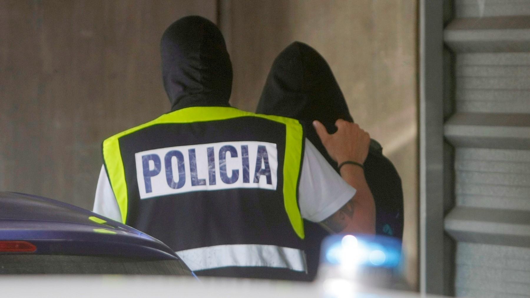 Un agente de la Policía Nacional con uno de los cuatro detenidos por el homicidio de Samuel Luiz. (Foto: Efe)