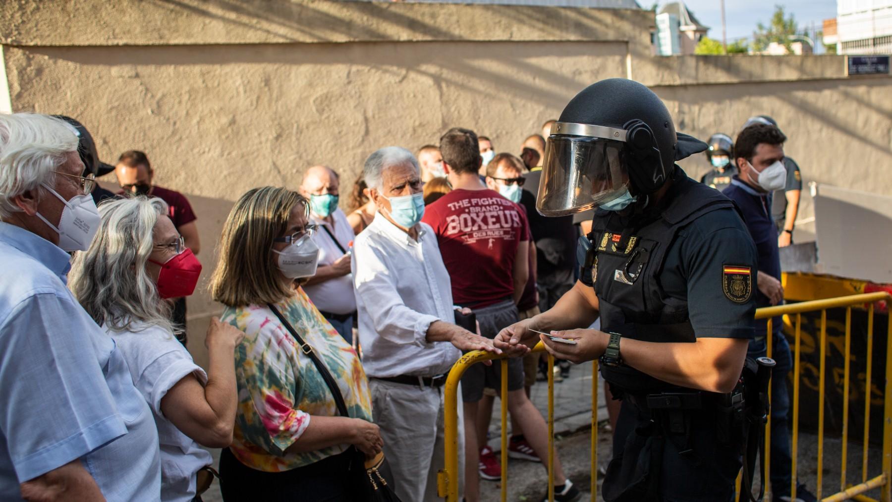 Un antidisturbios identifica a varias personas enfrente de la embajada de Cuba.