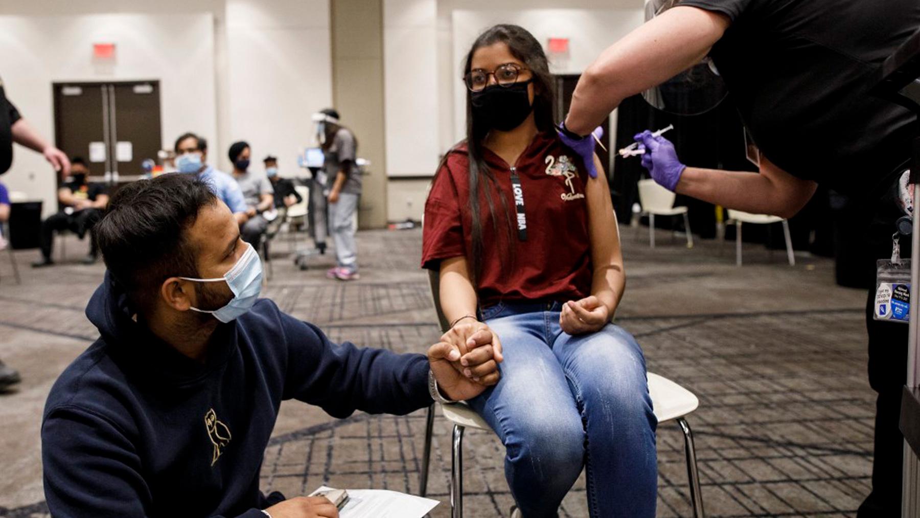 Una mujer se vacuna en Ontario, Canadá, agarrada de la mano de su pareja. Foto: AFP