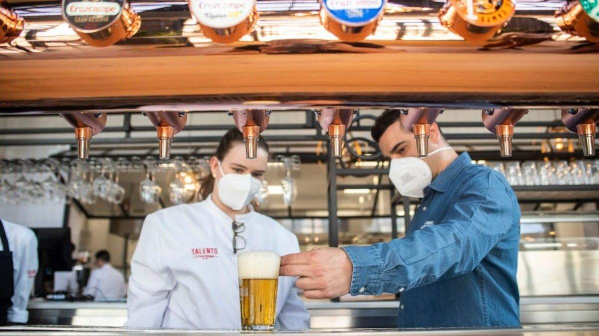 Dos camareros sirviendo una cerveza en su establecimiento (CRUZCAMPO).