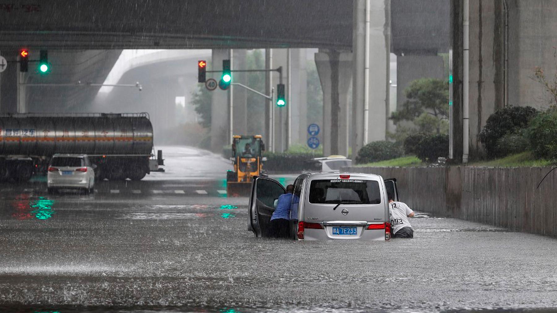 Dos personas tratan de sacar su coche de la inundación provocada por las lluvias en la provincia china de Henan. Foto: AFP