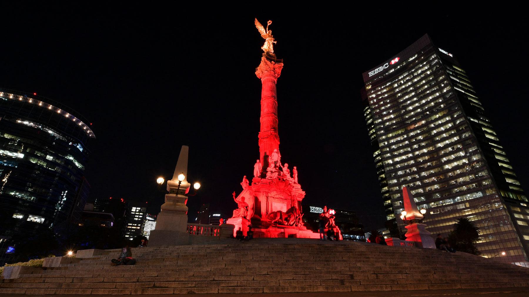 El famoso monumento mexicano de 'El ángel de la Independencia' iluminado de rojo por el día internacional de la lucha contra el SIda. Foto: AFP