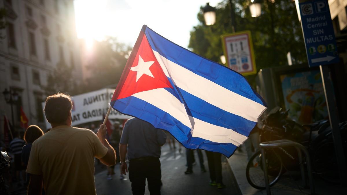 Personas portando banderas en una manifestación.