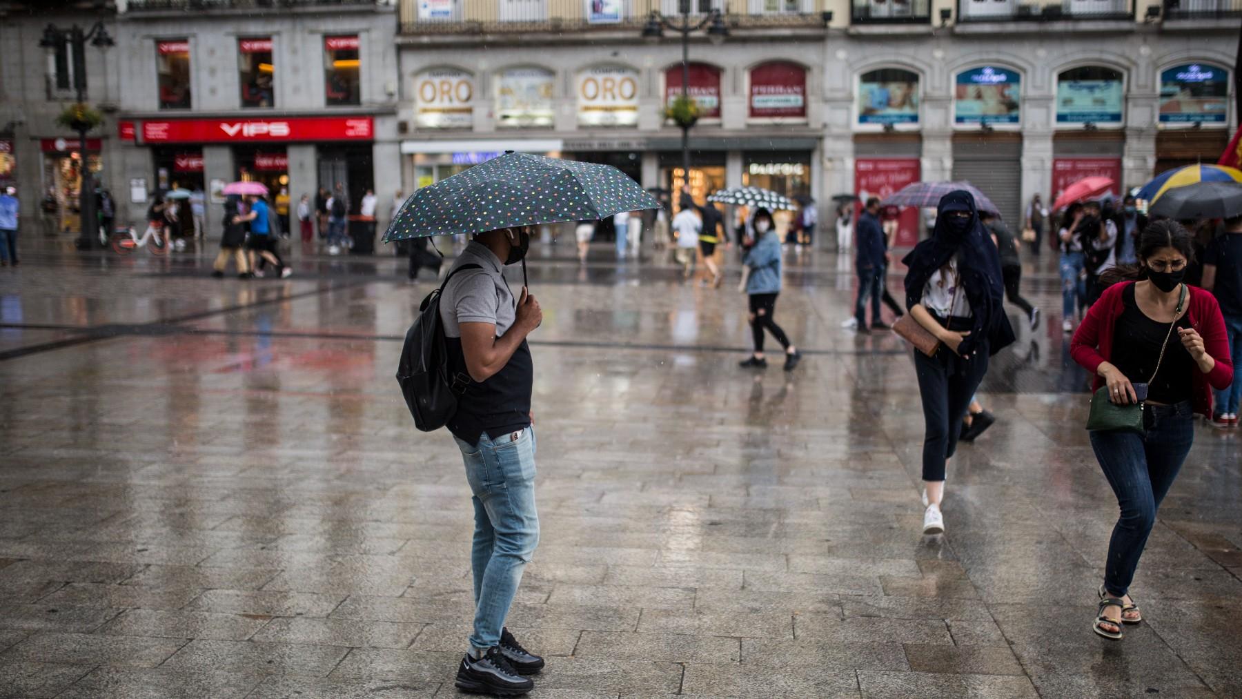 Ciudadanos se resguardan de la lluvia en Madrid.