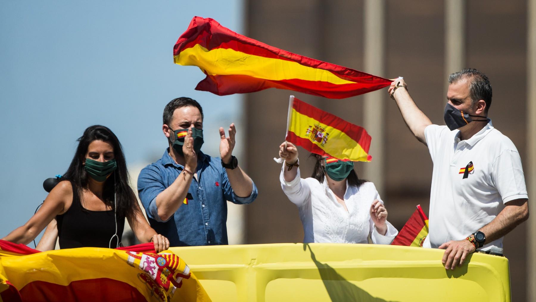 antiago Abascal y dirigentes de Vox con la bandera de España. (Foto Europa Press)