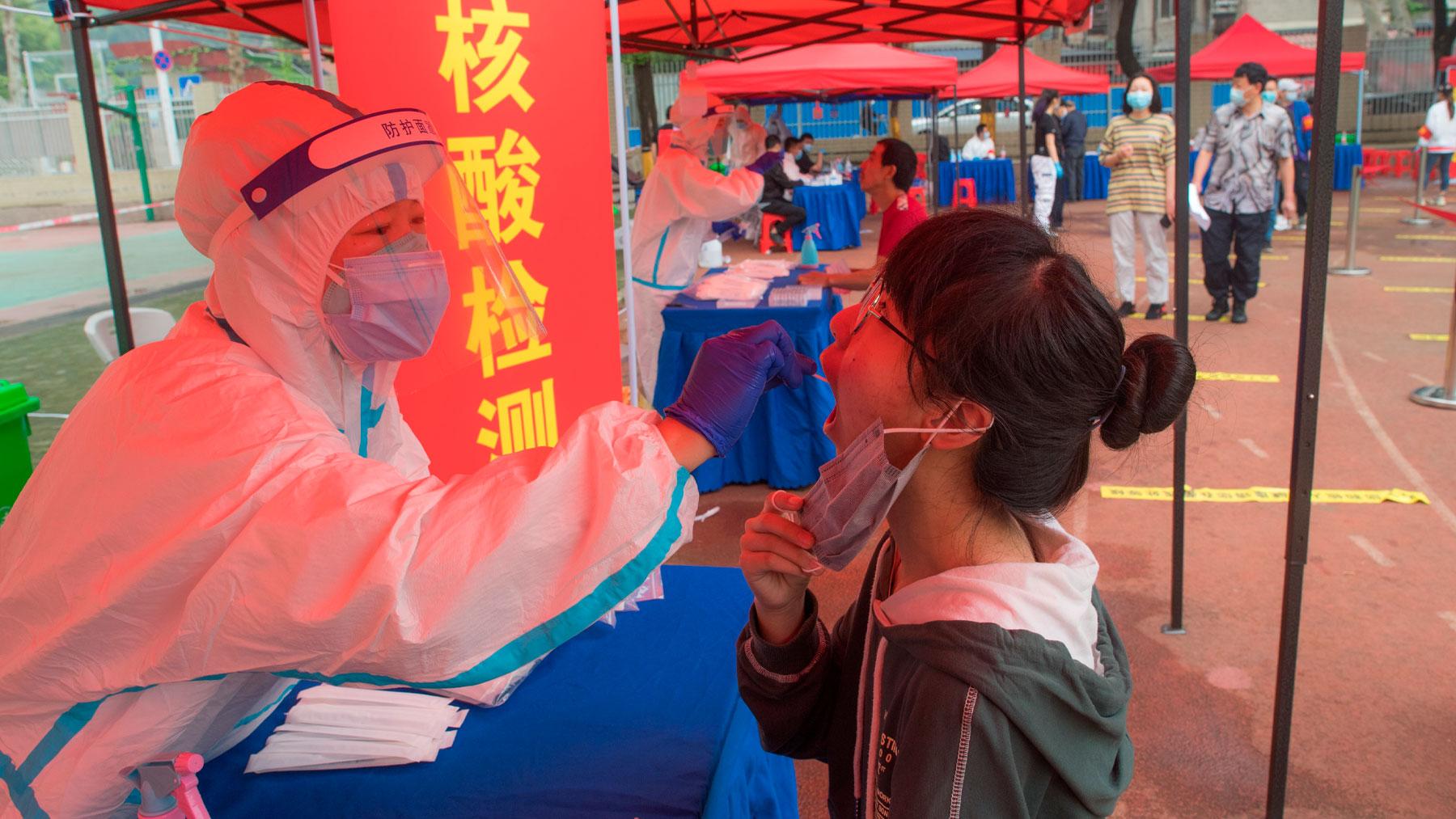 Un sanitario realiza una prueba Covid a una joven en Wuhan, China. Foto: EP