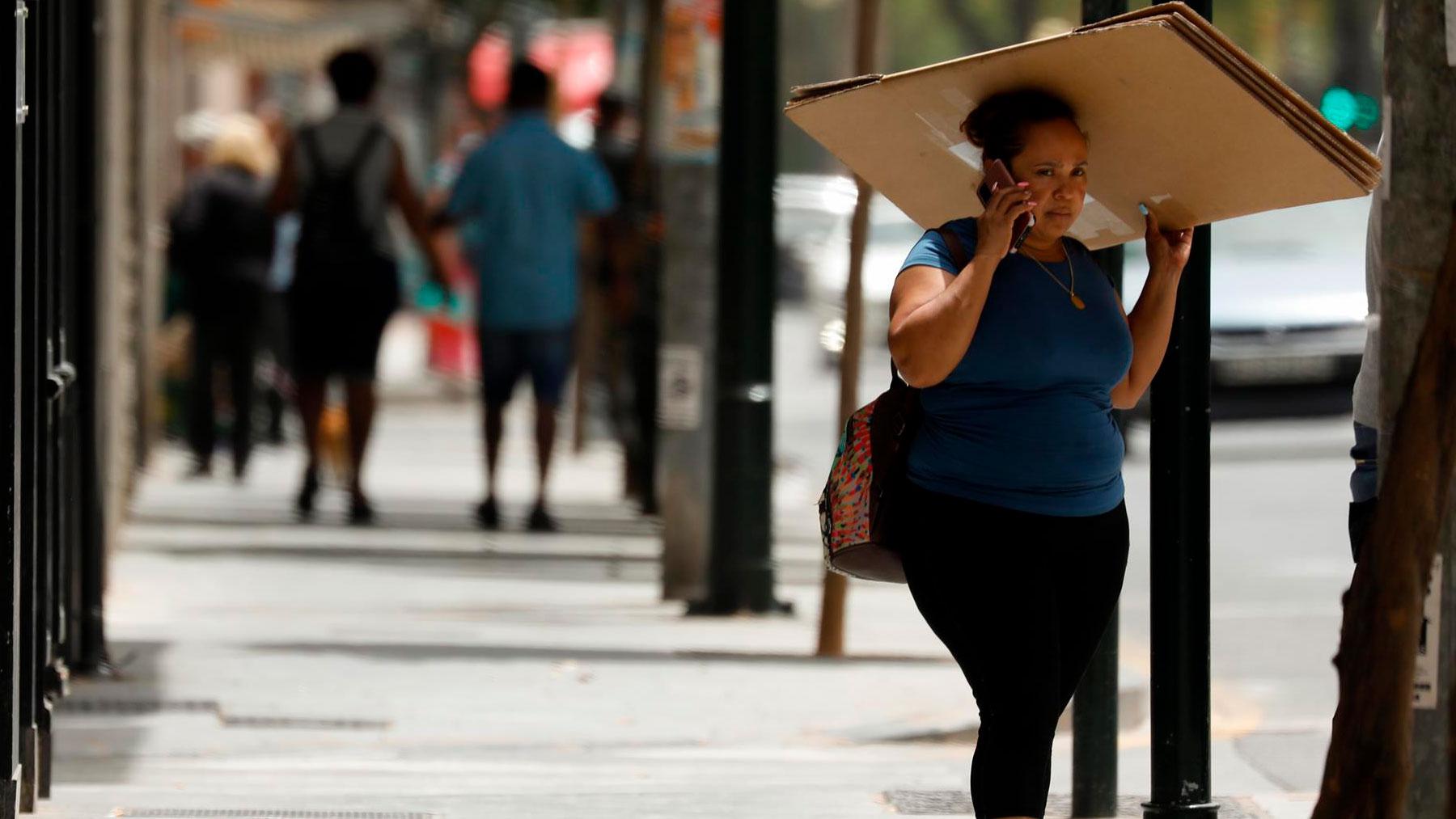Una mujer se resguarda del sol con un cartón. Foto: EP