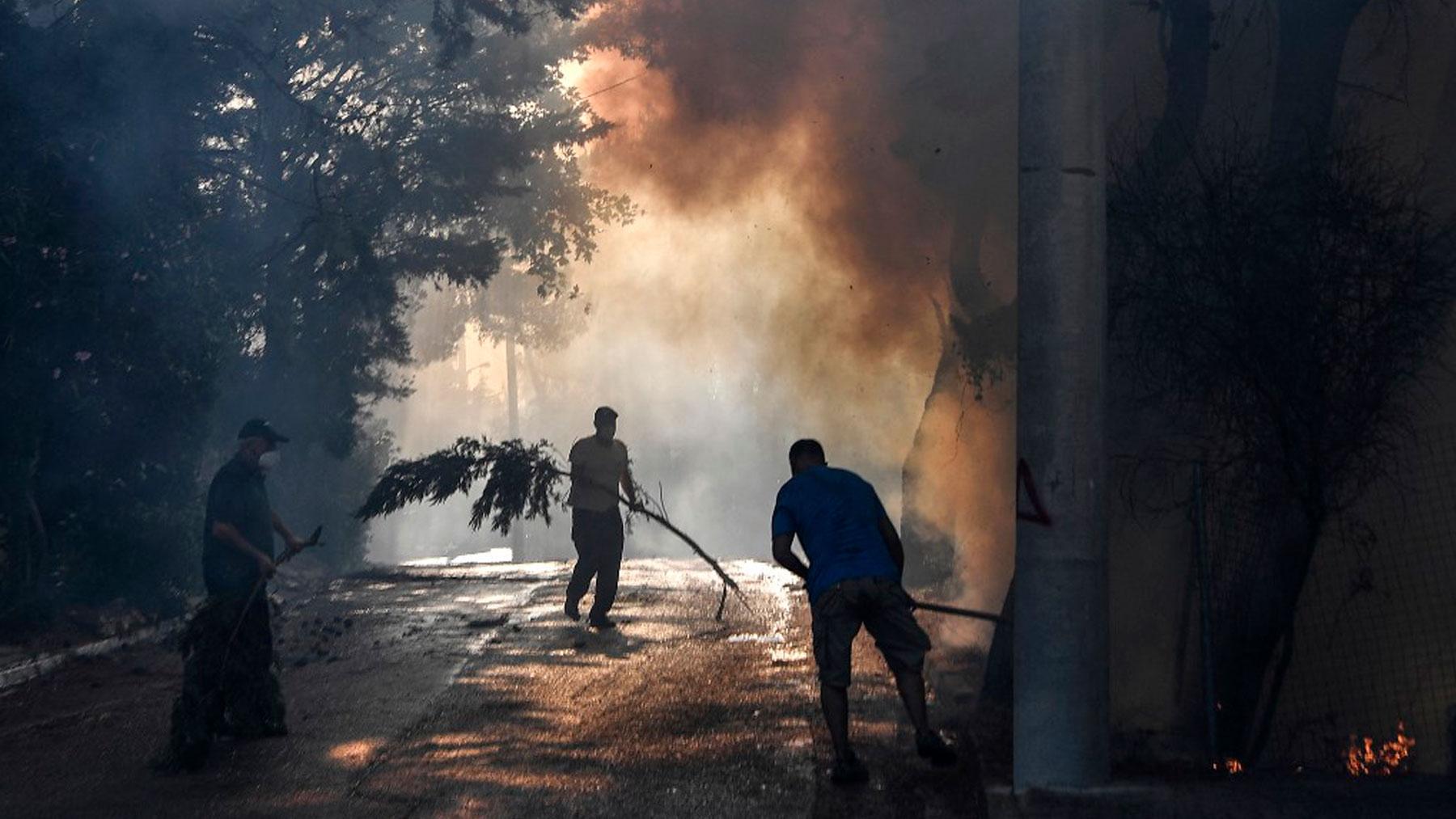 Vecinos de Thrakomakedones, una villa cercana al monte Parnitha, al norte de Atenas, se esfuerzan por apagar los puntos calientes de los incendios. Foto: AFP
