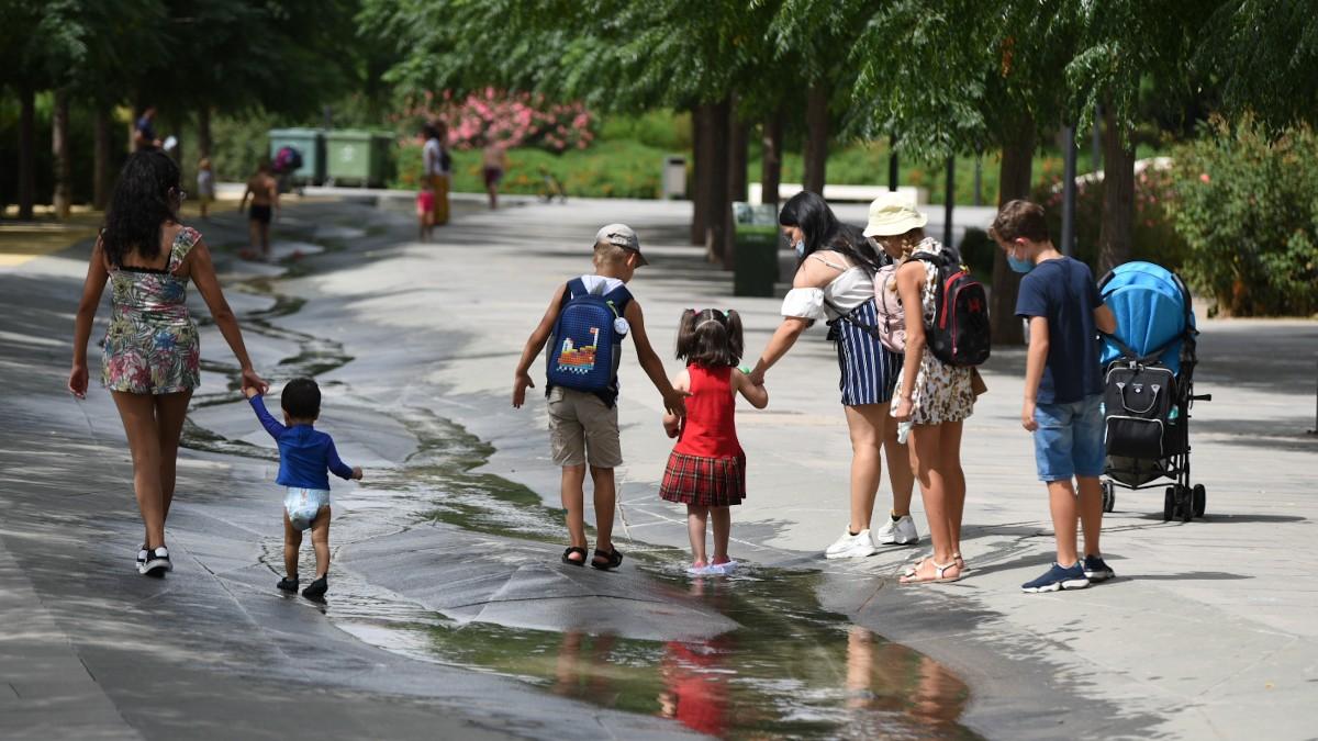 Varios niños paseando por un arroyo.