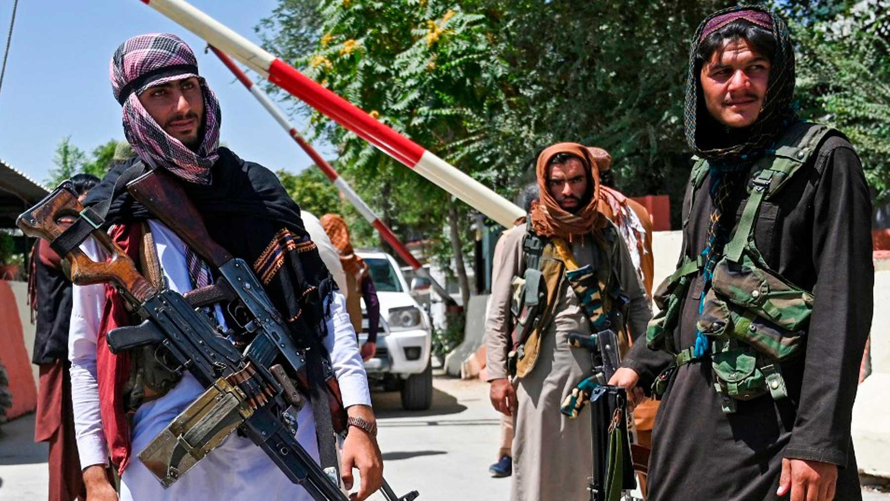 Tres talibanes custodian armados una frontera en Kabul. Foto: AFP