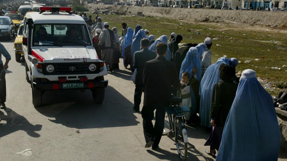 Una ambulancia junto a una fila de mujeres con burka en Kabul, Afganistán.